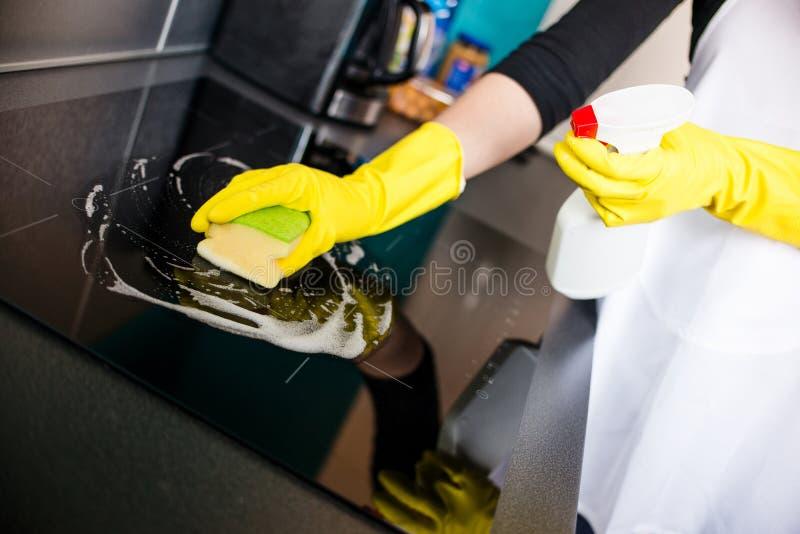 清洗电磁炉的妇女的手 免版税图库摄影