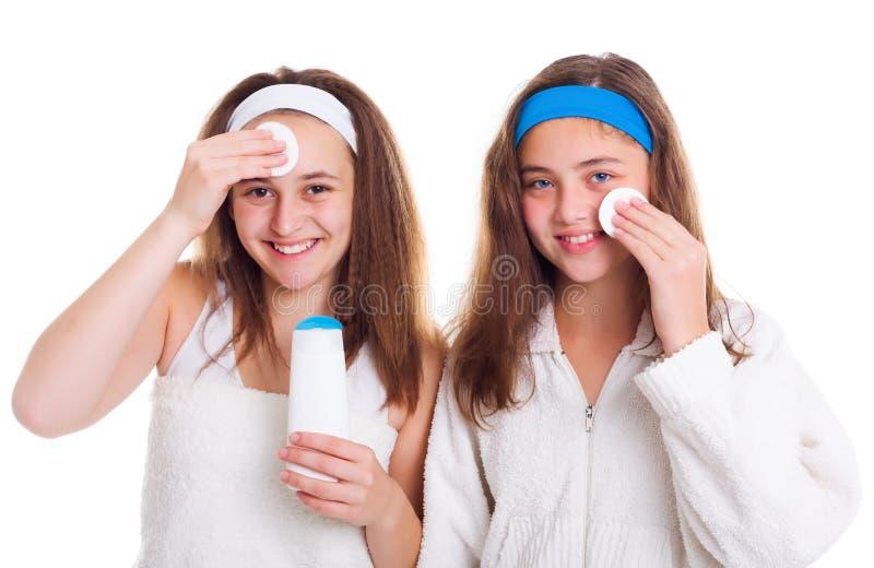 清洗他们的女孩面孔与补剂化妆水 库存图片