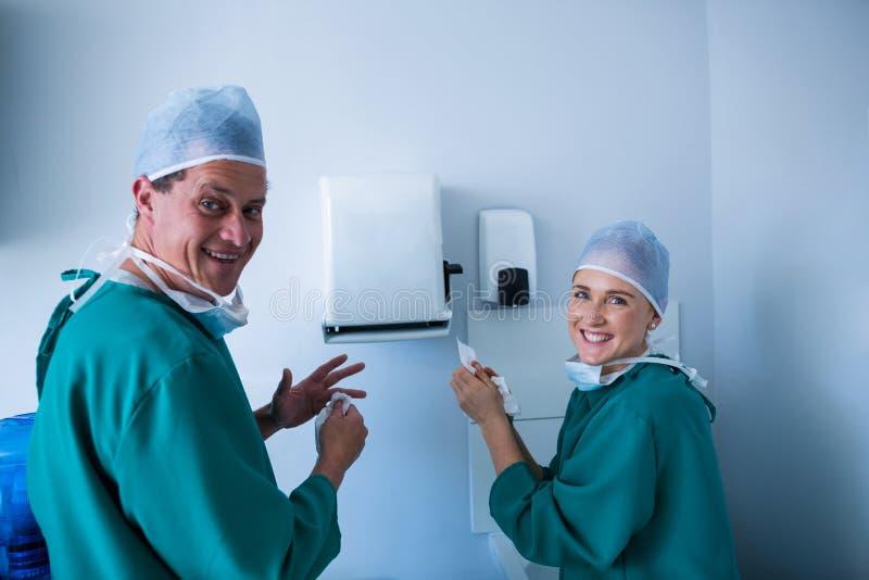 清洗他们的手的愉快的外科医生画象在操作以后 库存照片