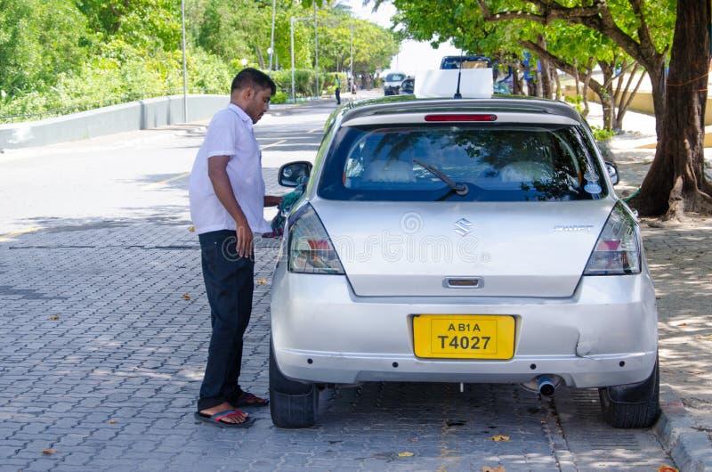 清洗他的汽车的出租汽车司机 免版税库存图片