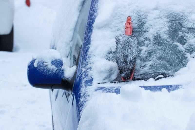 清洗的汽车的刷子从在挡风玻璃的雪 图库摄影