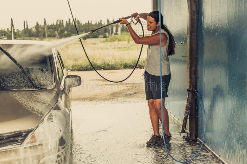 清洗他的汽车的年轻人使用在自助洗车的高压水 免版税图库摄影