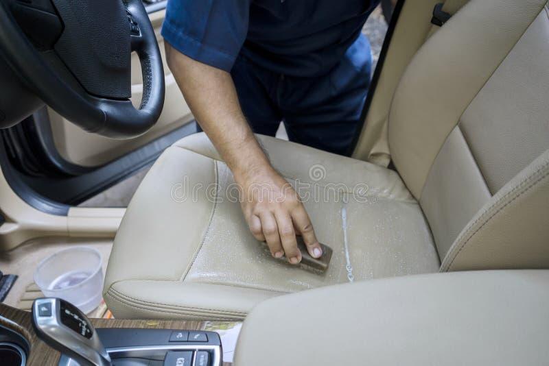 清洗皮革汽车座位的手 图库摄影