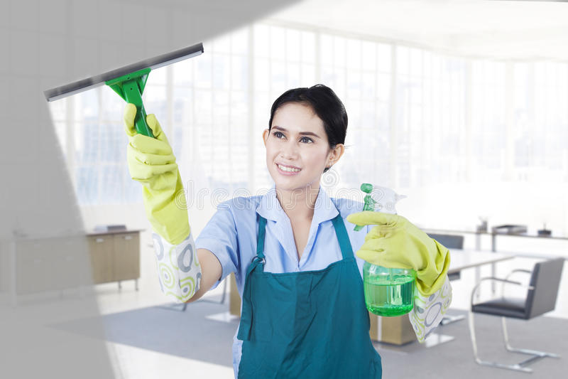 清洗窗口的女性佣人 免版税库存图片