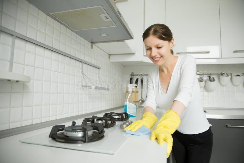 清洗st的年轻微笑的妇女佩带的橡胶黄色手套 图库摄影