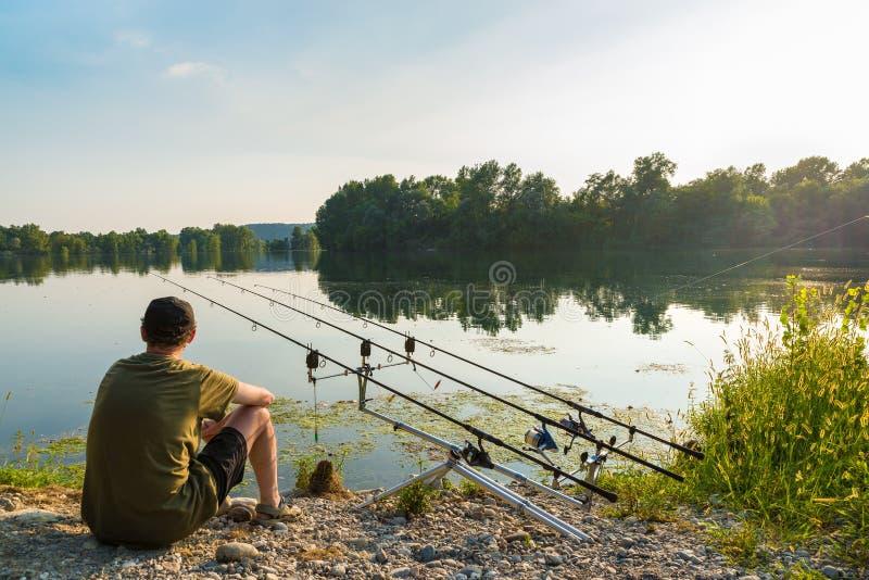 渔冒险,鲤鱼渔 钓鱼者钓鱼与在淡水的carpfishing的技术 免版税库存照片