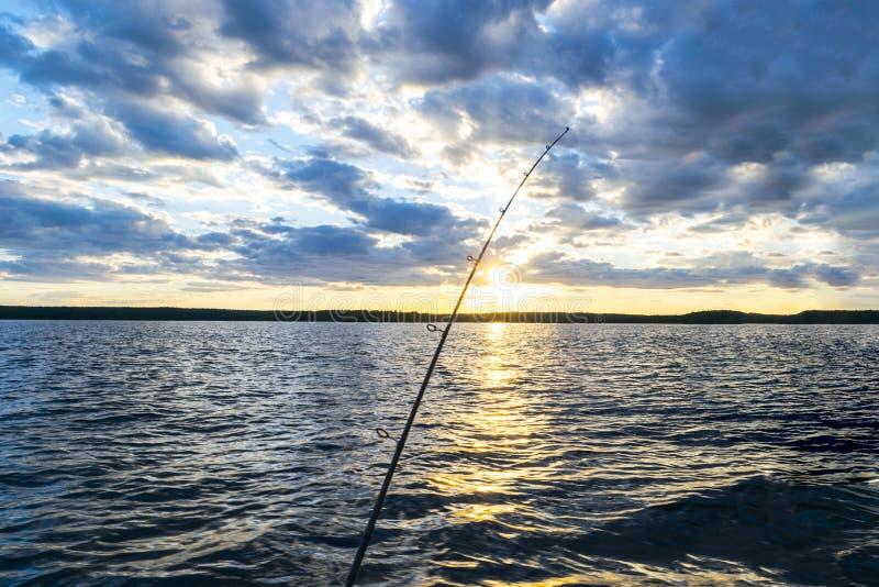 渔在日落期间的路剪影 反对海洋的结尾杆日落的 在盐水小船的钓鱼竿在渔场天期间  库存图片