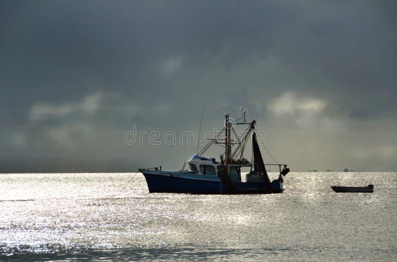 渔在港口风雨如磐的日落的拖网渔船小船 免版税库存照片