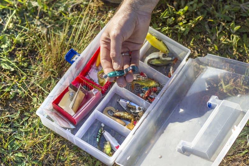 渔夫从箱子选择橡胶诱饵 免版税图库摄影
