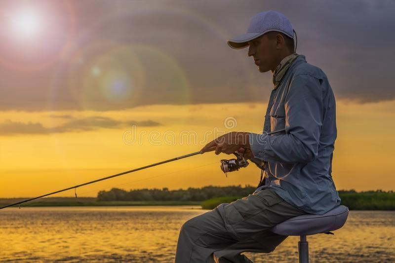 渔夫剪影小船的 有钓鱼竿的人在多云日落背景 库存图片