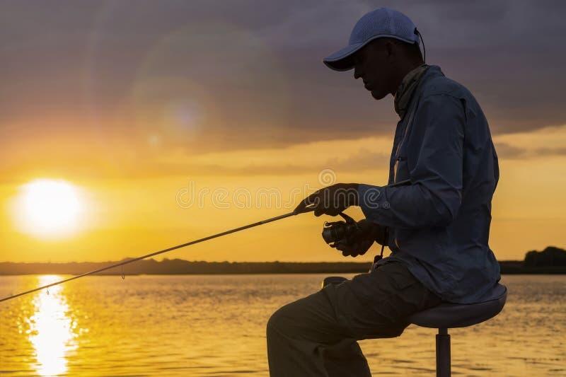 渔夫剪影小船的 有钓鱼竿的人在多云日落背景 免版税库存图片