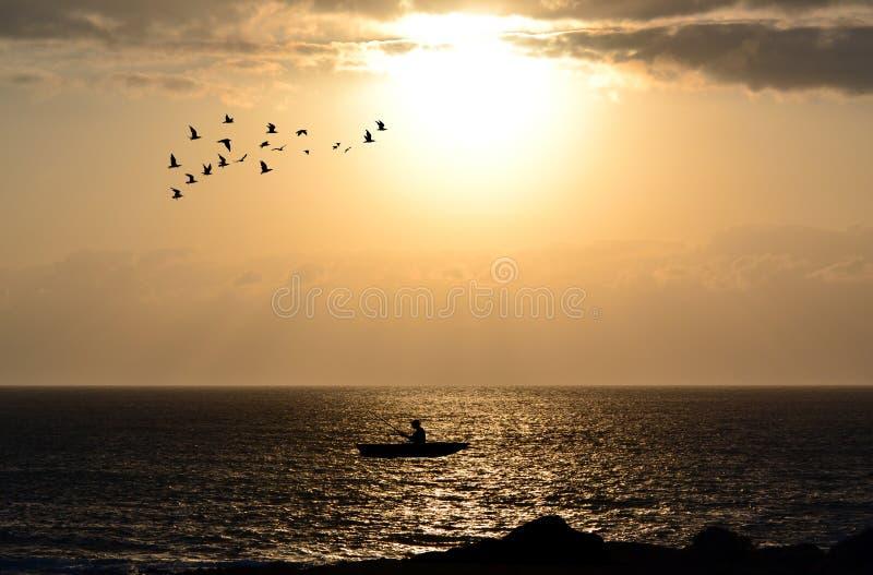 渔夫剪影有他的小船的 库存照片