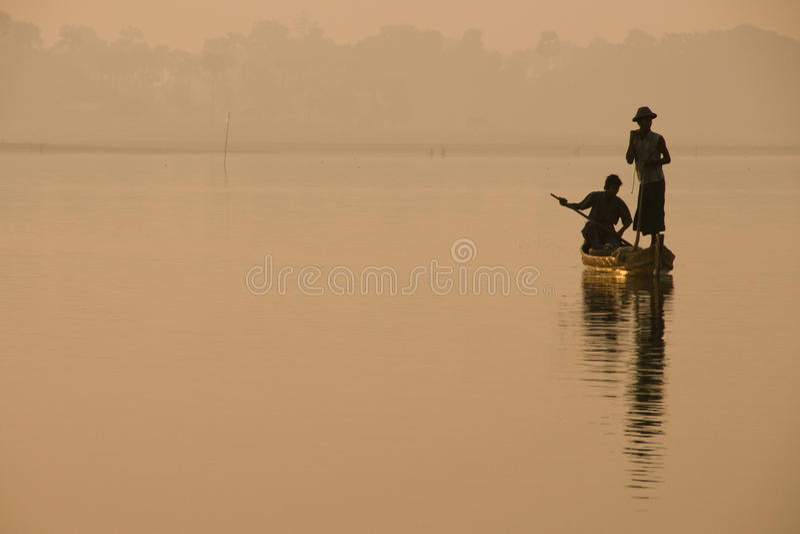 渔夫剪影金黄早晨光的与一名脚划船者,缅甸的Taungthaman湖的 免版税库存照片