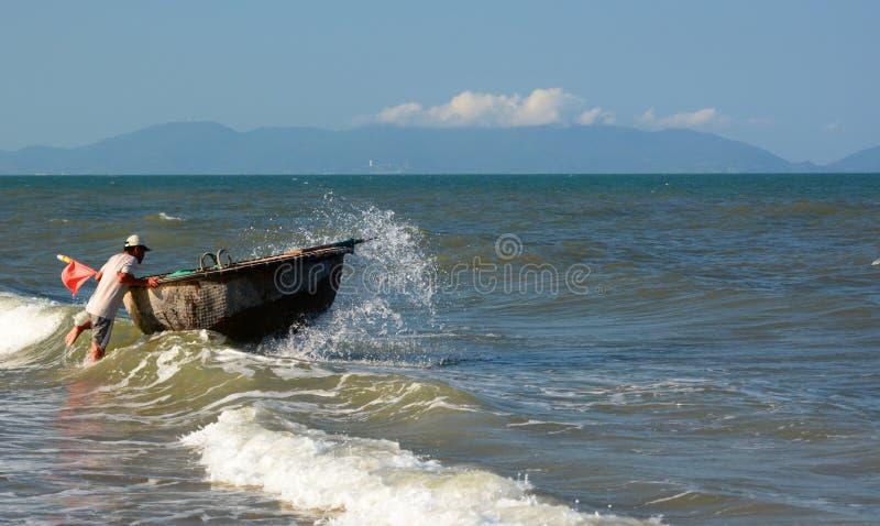 渔夫和他的传统圆的小船( 桐树chai) 轰隆海滩 的Hoi 越南 图库摄影