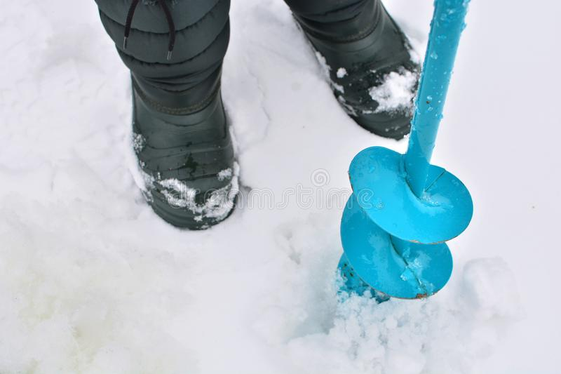 渔夫在一个冻湖做一个孔 免版税库存图片