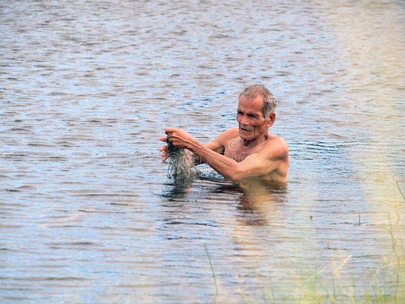 渔夫在乡下河围网的狩猎鱼 免版税图库摄影