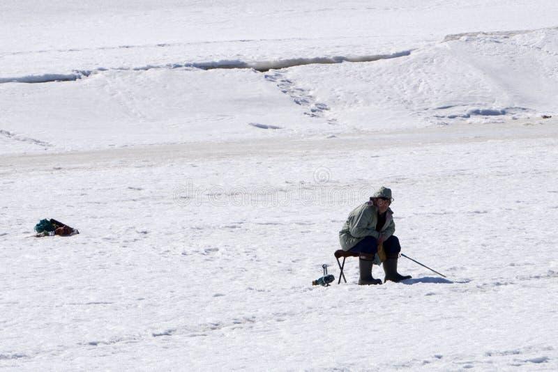 渔夫在冬天坐并且抓在一把椅子的鱼在毛毡起动-俄罗斯Berezniki 2018年4月7日的冰 库存图片