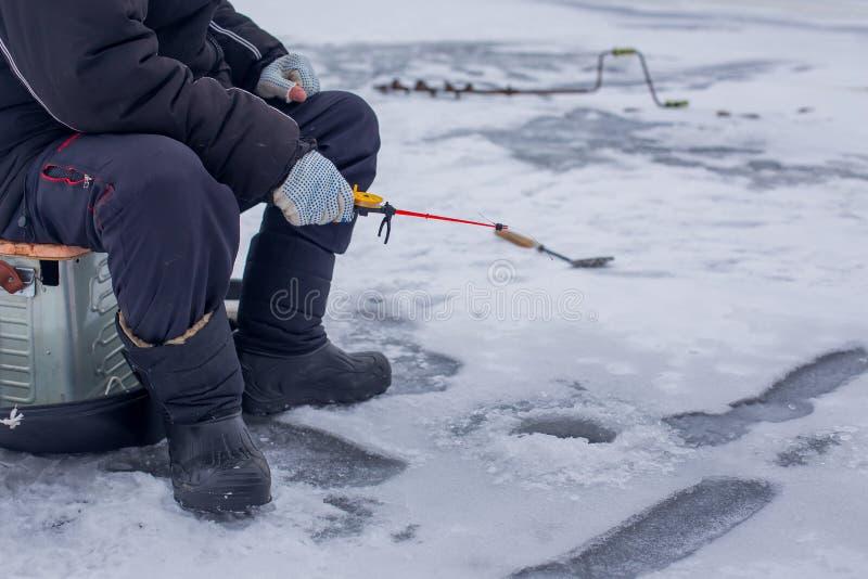 渔夫在冬天钓鱼竿的抓住鱼的特写镜头手在有孔的冻河 免版税库存图片