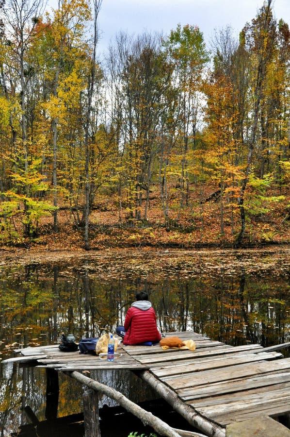 渔夫在秋天森林抓鱼在湖 免版税库存照片