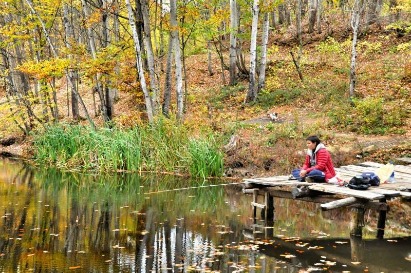 渔夫在秋天森林抓鱼在湖 库存图片