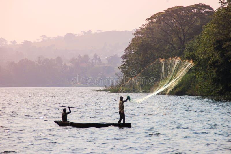 渔夫在维多利亚湖投掷网 免版税库存照片