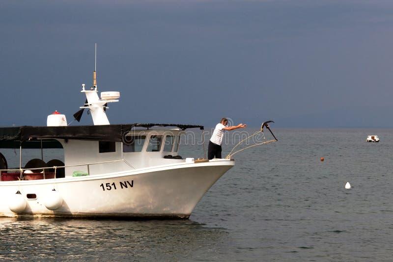 渔夫在返回投掷船锚从渔以后 免版税库存图片