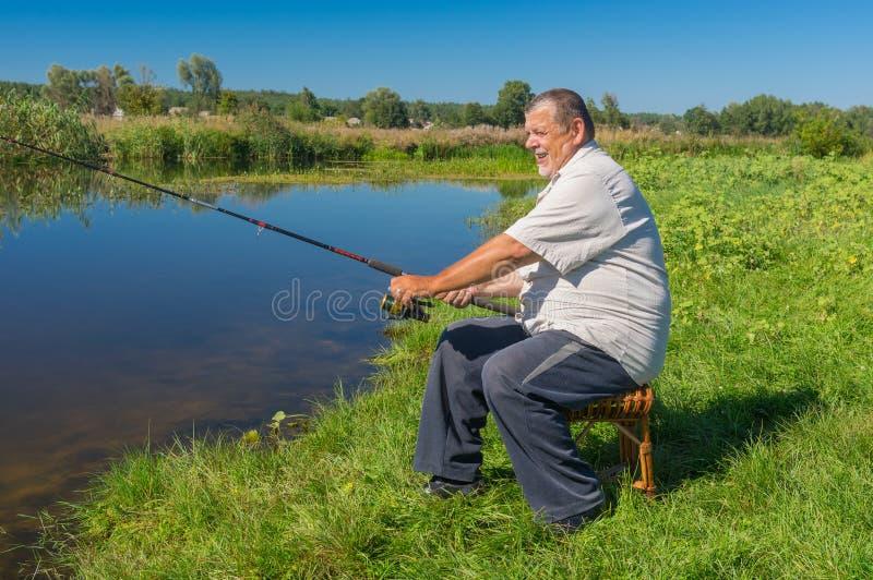 渔夫坐与实心挑料铁杆的一把柳条凳子和在小河Merla准备抓鱼在中央乌克兰 免版税图库摄影