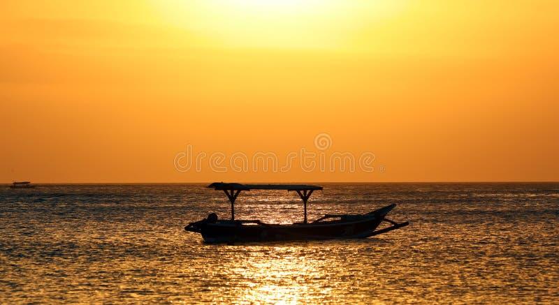 渔夫小船在巴厘岛,在金黄日落期间的印度尼西亚 看起来金子的海洋和天空 库存图片