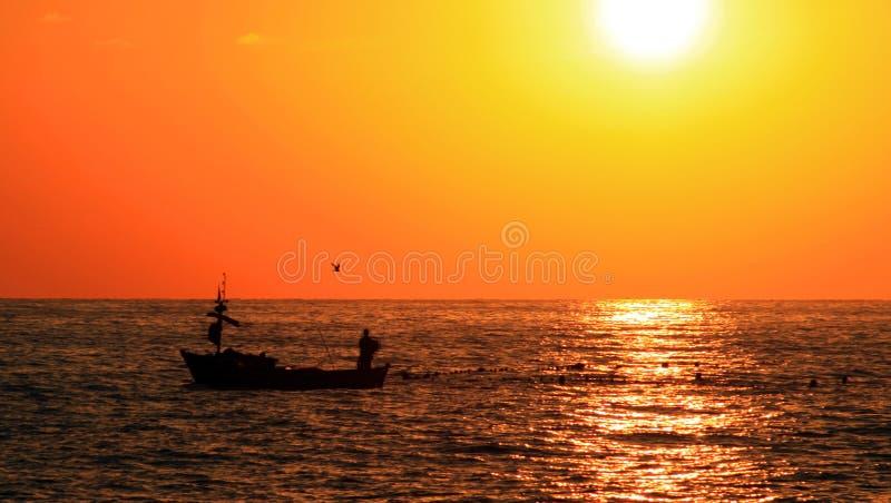 渔夫小船的人在日落 免版税库存图片