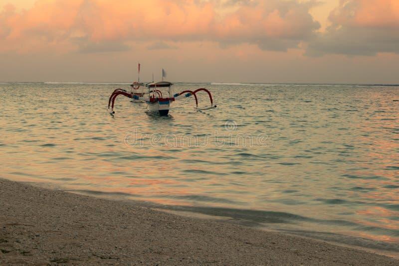 渔夫小船jukung 在海滩的传统渔船在日落期间 Pandawa海滩,巴厘岛,印度尼西亚 免版税库存图片