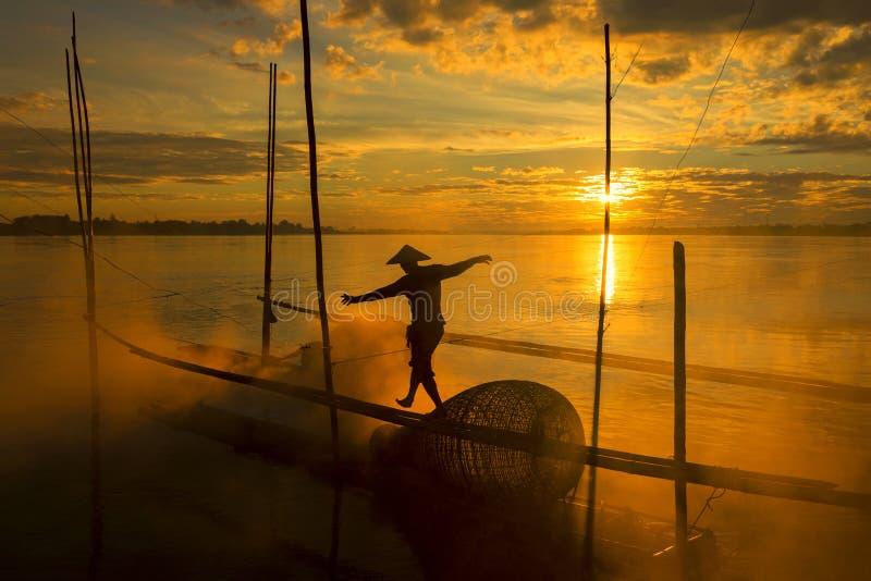 渔夫工作湄公河木筏的在sunrisภ³期间 库存照片