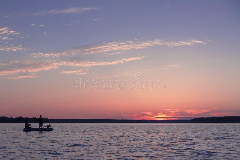 渔夫抓在美好的日落的背景的鱼 库存图片