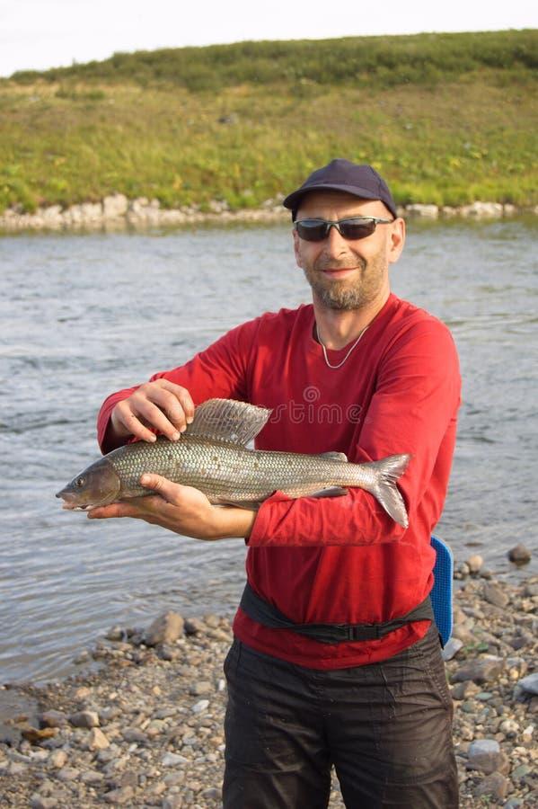 渔夫捉住了一个大河鳟 免版税库存图片