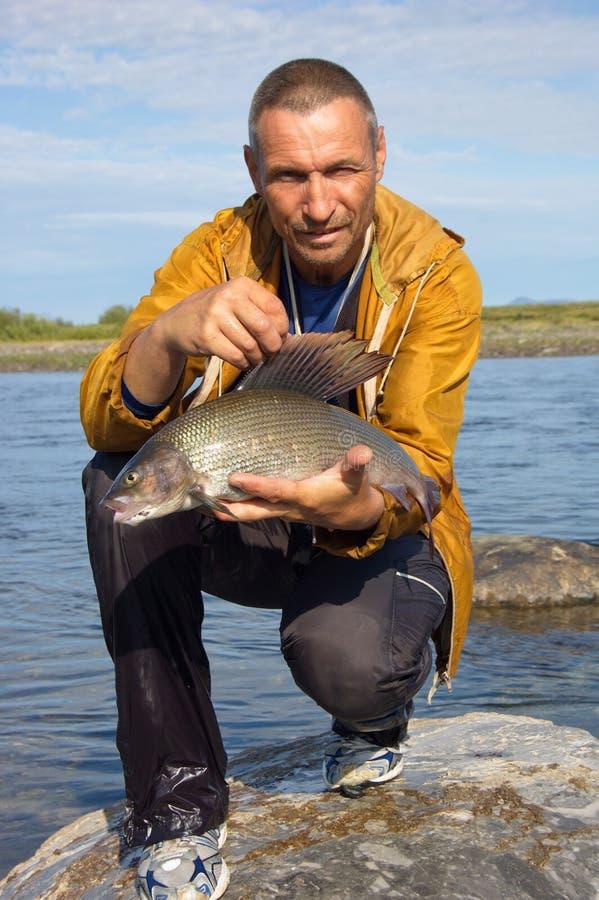 渔夫捉住了一个战利品河鳟 库存图片