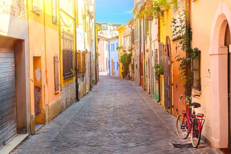 渔夫有五颜六色的房子的圣Guiliano和自行车村庄的狭窄的街道在清早在里米尼,意大利 图库摄影