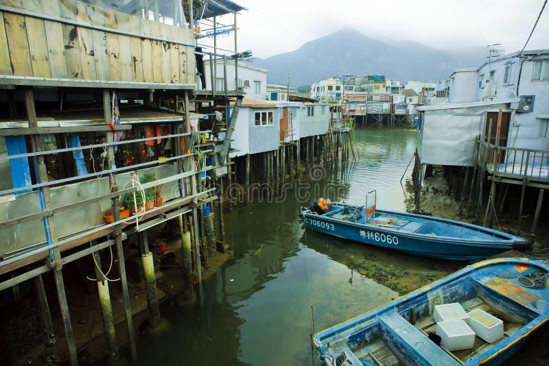 渔夫河船在恶劣的村庄临近木高跷的金属房子 库存图片
