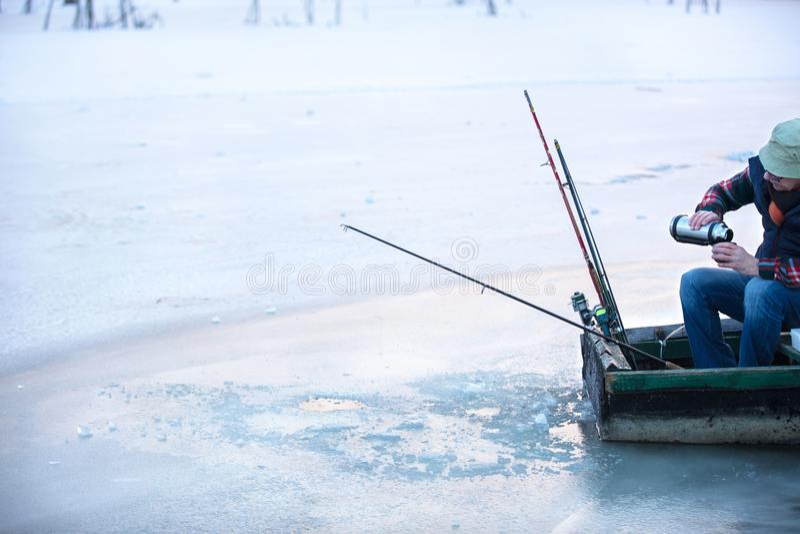 渔夫渔在冬天和饮用的发球区域的冻河 图库摄影
