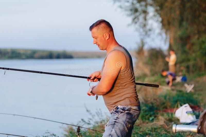 渔夫短冷期为捉住的鲤鱼做准备在湖在夏天 免版税库存照片