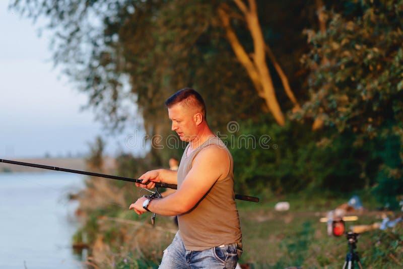 渔夫短冷期为捉住的鲤鱼做准备在湖在夏天 免版税库存图片