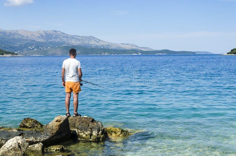 渔夫简而言之在海滨岩石的 库存图片