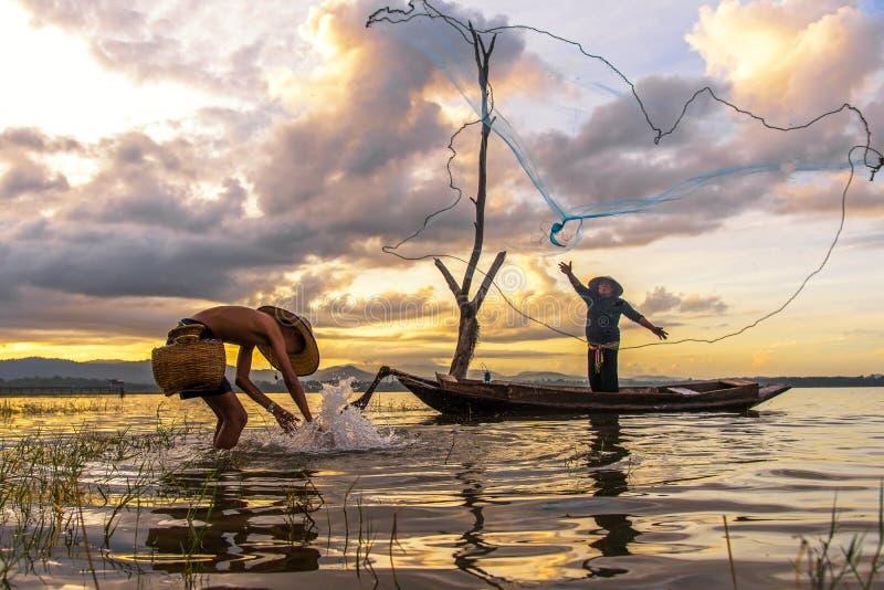 渔夫行动,当在湖的捕鱼网小船的阳光早晨和剪影渔夫的, 图库摄影