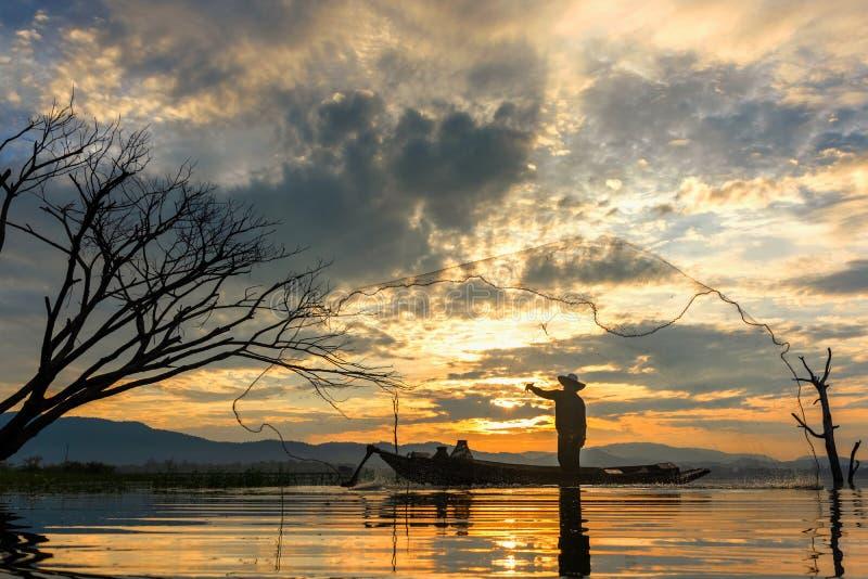 渔夫行动,当在湖的捕鱼网小船的阳光早晨和剪影渔夫的, 库存图片