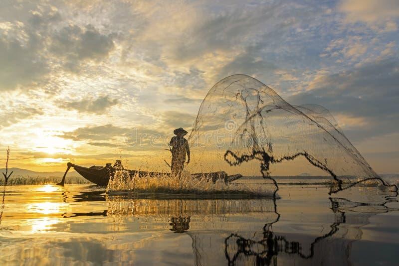 渔夫行动,当在湖的捕鱼网小船的阳光早晨和剪影渔夫的, 免版税库存图片
