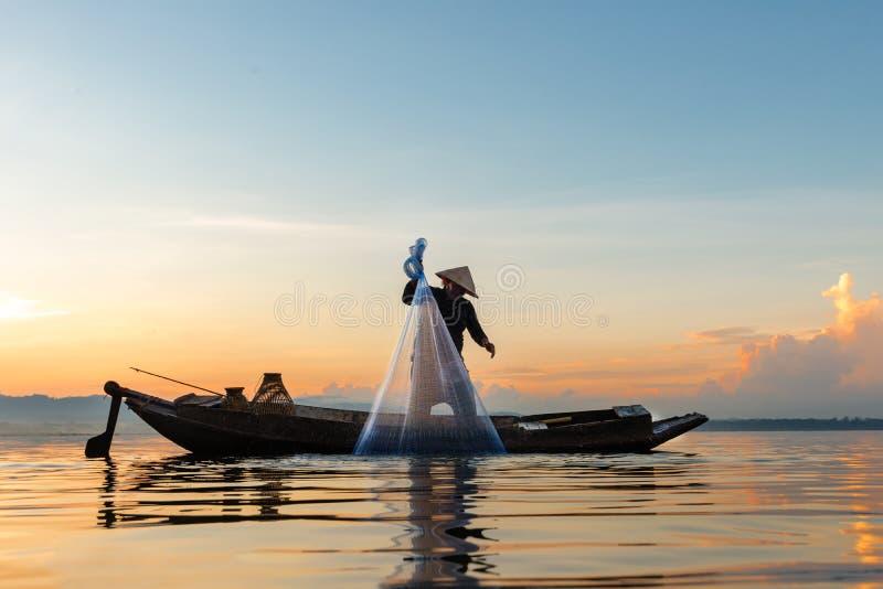 渔夫行动,当在湖的鱼网户外阳光早晨和剪影渔夫的在小船, 图库摄影