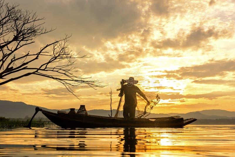渔夫行动,当在湖的鱼网阳光早晨和剪影渔夫的室外在小船, 图库摄影