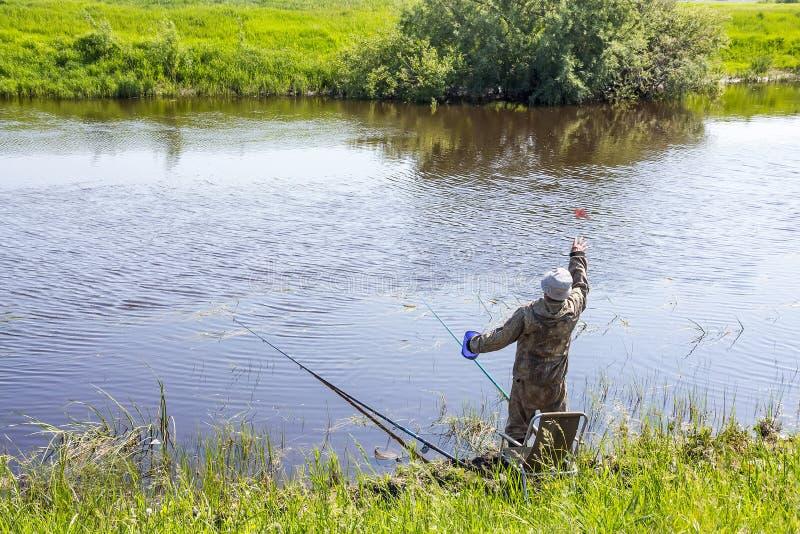 渔夫诱剂鱼在钓鱼的河与浮游物标尺 库存图片