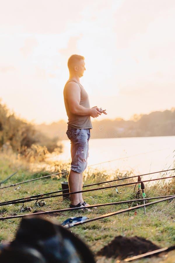 渔夫进口乘在湖的小船引诱钓鱼的 免版税图库摄影