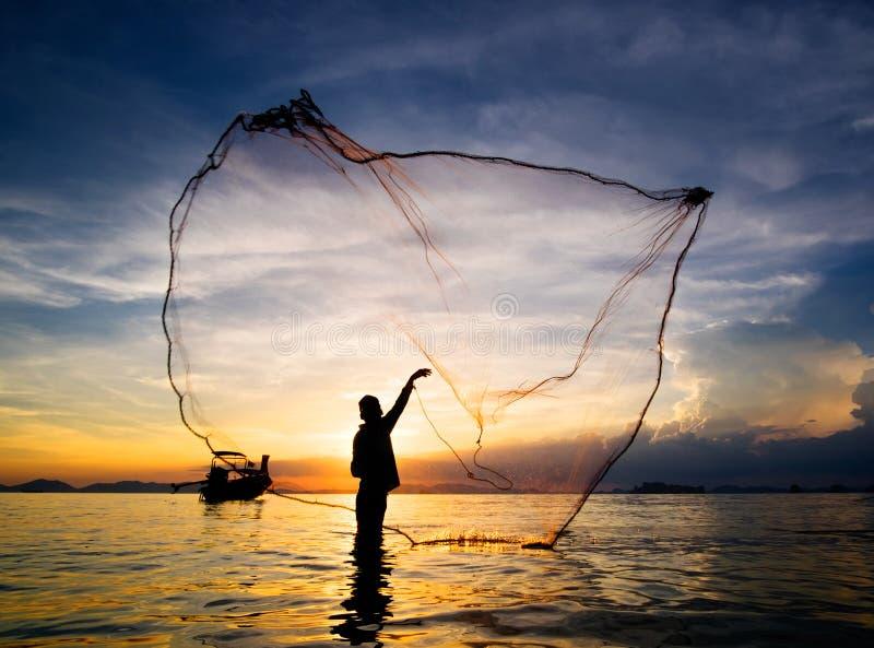 渔夫铸件捕鱼网剪影到海里 免版税库存图片