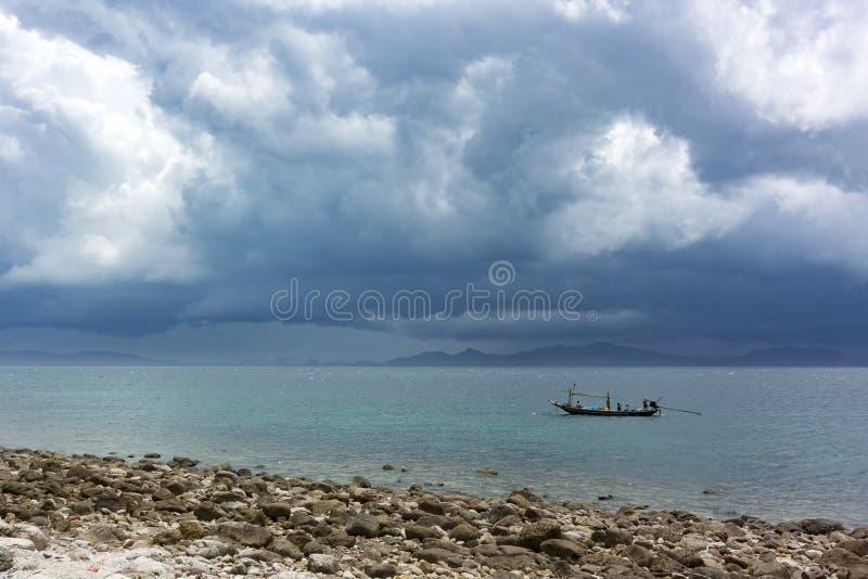 渔夫从大雨风暴的小船皮 库存图片