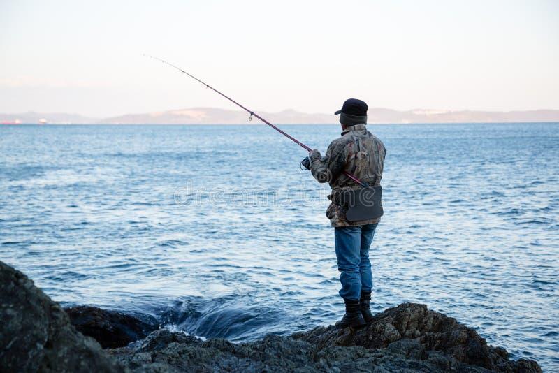 渔民在礁石上钓鱼 免版税库存照片